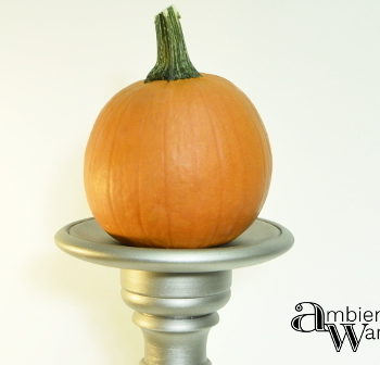 Wooden pedestal from an old table lamp holding a pumpkin