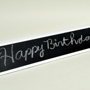 Happy Birthday written on chalkboard name plate
