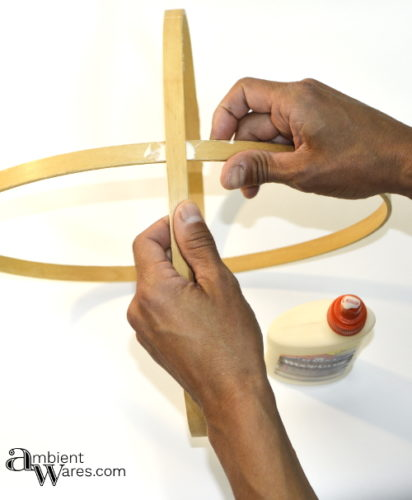 Smearing glue between the 2 embroidery hoops to secure before making the 4 sided mobile