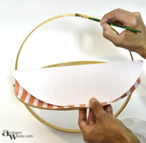 Spreading glue on embroidery hoop edges to adhere scrapbook paper