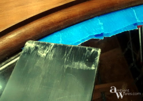 Tucking_in_the_tape_under_the_frame_Easy_DIY_Painted_Wooden_Framed_Mirror_ambientwares.com