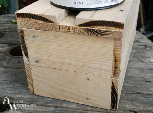 A metal basket gets a DIY pallet wood insert. Two baskets in one! For this and more unique project ideas, visit AmbientWares.com