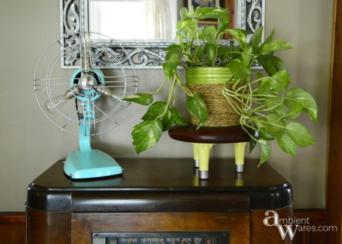 Come see how a wooden seat and old bed frame feet were combined to make a cute mid-century vibed plant stand! For this and more unique project ideas, visit AmbientWares.com!